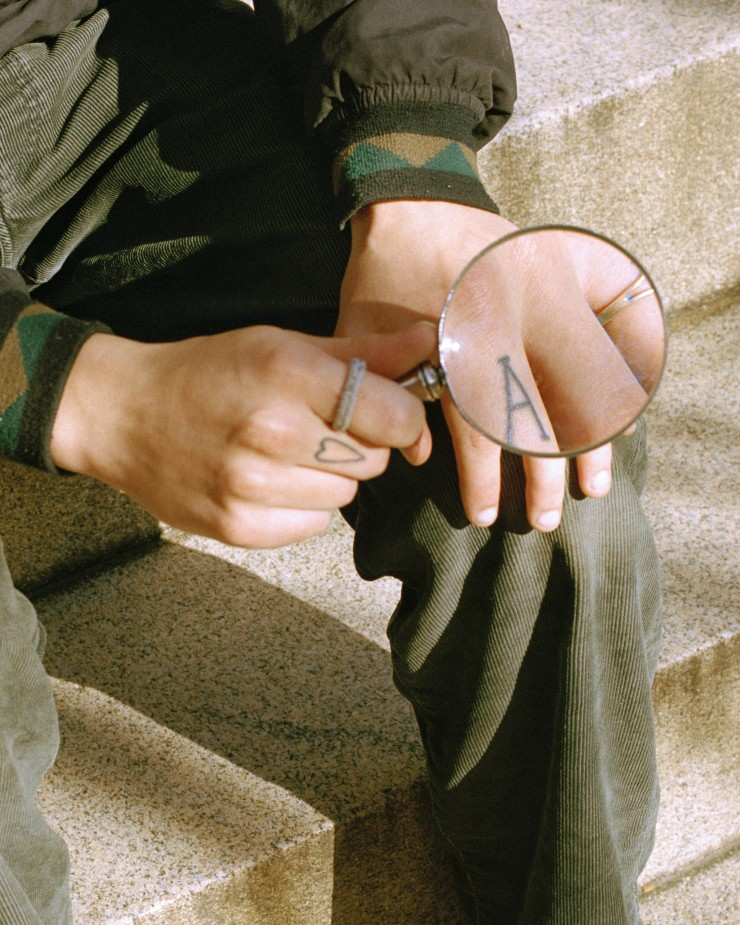 "This photograph is a portrait of someones hands. He's sitting on steps, holding a magnifying glass up to his left hand, focusing on his ""A"" tattoo on his middle finger. On his right hand, which is holding the magnifying glass, he has a heart tat"