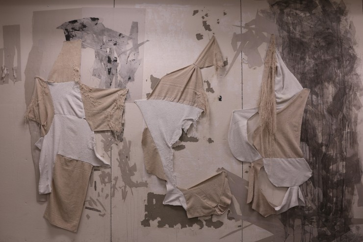 white and beige towels that have been used are cut into various shapes and sewn together to make a different form. they are displayed on the wall. Some areas of the fabrics are distressed by each fibers.