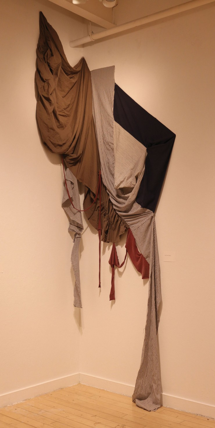 used bed sheets and other fabrics cut into different shapes and reconstructed. The fabric piece is hanging from a wall that forms a corner.