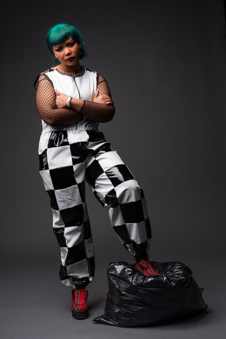 Model is wearing a horror punk inspired garment consisting of a black and white checkered jumpsuit made from vinyl fabric scraps. At the shoulders the garment is laced with shoelaces.