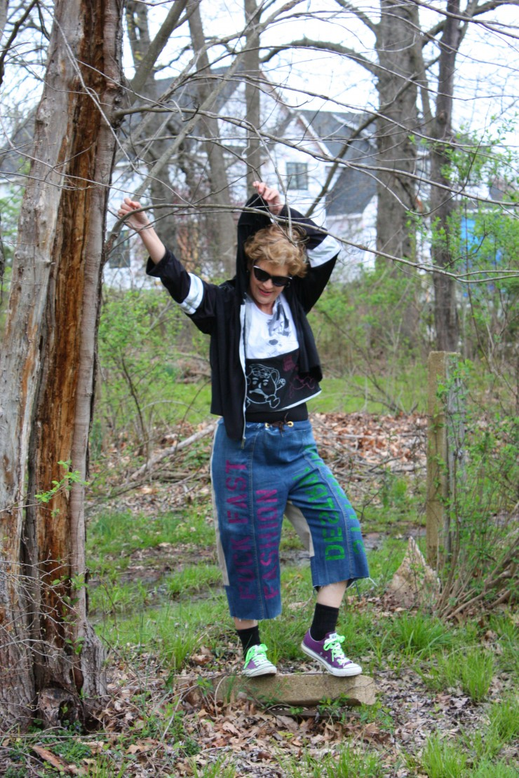 Model is wearing a ska punk inspired outfit consisting of a t-shirt, cargo-jean cutoff pants and a jacket. The t-shirt is made from multiple screen-printed graphic t-shirts. The pants front are made from jeans and the back from cargo pants and jeans. Ther