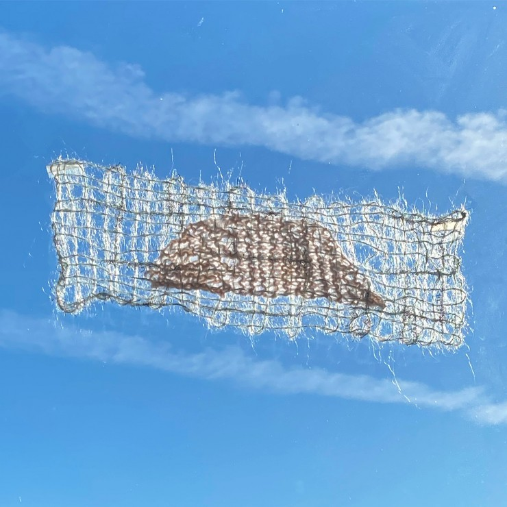 A narrow rectangular weaving made with fluffy yarn has a knit shape of a little hill in the center. It is framed between two contrails on a blue sky.