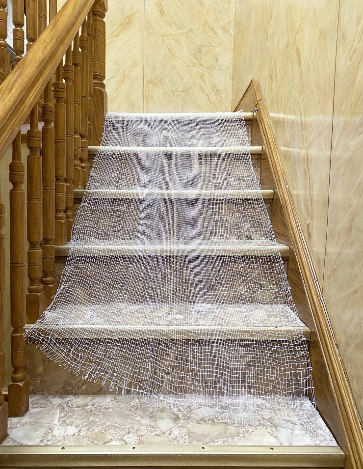 The weaving cascades down a residential indoor staircase with wooden railing, faux marble wall, and vinyl flooring. The weaving fits perfectly down the stairs because it was woven on a window that also matches the.
