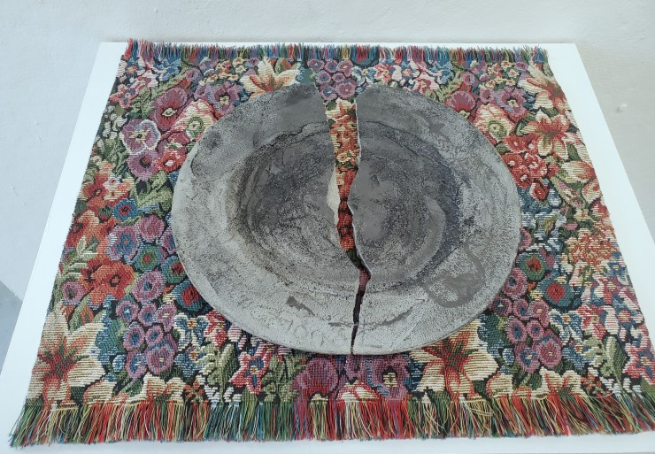 A plate on a placemat. The plate is made of cement with a pattern of lace pressed into it. The lace has been accentuated with charcoal so that the imprints are dark. The plate is upside down on the mat, the bottom is made of an imbedded tin lid. The lid i