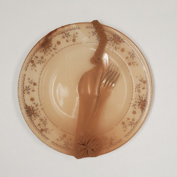 A diner plate, covered in pantyhose. There is a spoon, knife, and two forks inside a sack made of the hoes, that is braided at the top, connecting it to the backside of the plate.
