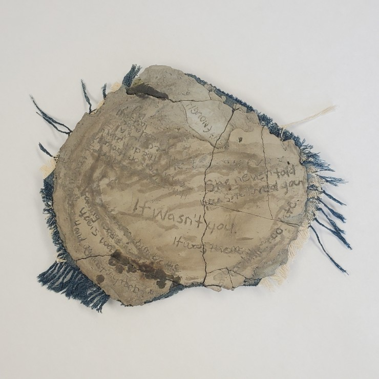 """A broken cement plate on a piece of denim that is frayed and braids on the edges. The Cement has cracks and writings etched into it. Samples of the writing, """"it wasn't you. It was them."""" """"She never told you she loved you."""" Much of the writing is covered o"""