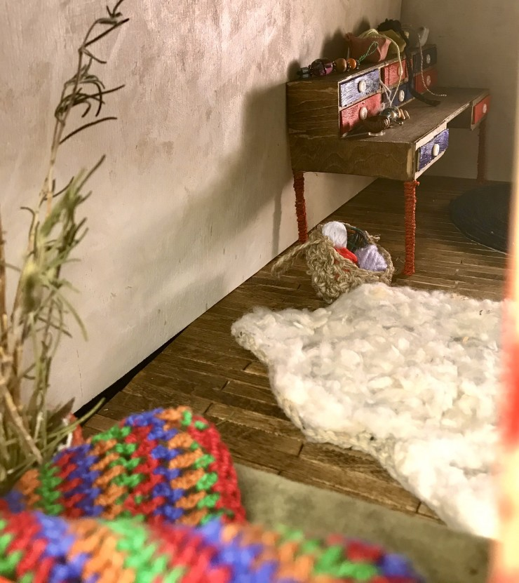 Photos of a handmade, three-dimensional stop motion set. It is a miniature single-room cabin with many quaint little details and a cozy feel. Two windows and an open door let warm light into the room. Among the larger furniture is a bed with a quilted com