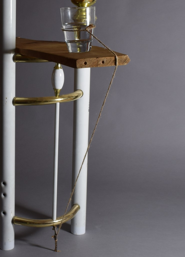 A plank of milled found wood horizontally balanced on a found metal bed frame standing vertically. One glass half-filled with water is placed on one end of the wooden plank and a twine tied around the glass on one end is tied to a twig, which is placed un