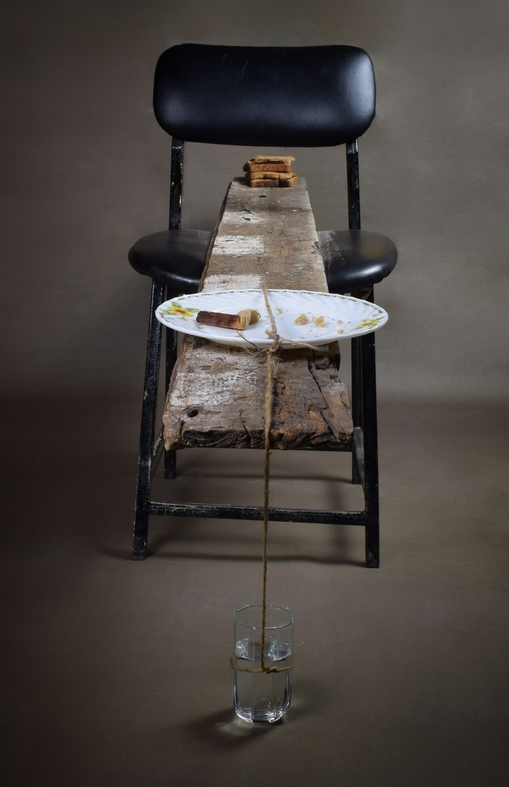 A wooden plank on the seat of a steel chair, balanced by loaves of bread on one end and a plate with breadcrumbs on the other. A string of twine is tied to the plate on one end and a glass that is placed beneath the plank and half-filled with water.
