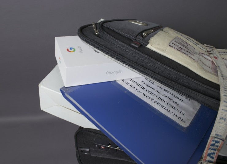 A travel bag over-packed with boxes of American electronic items and immigration documents balanced on a chipped away wooden bar stemming from inside a glass slightly filled with water.