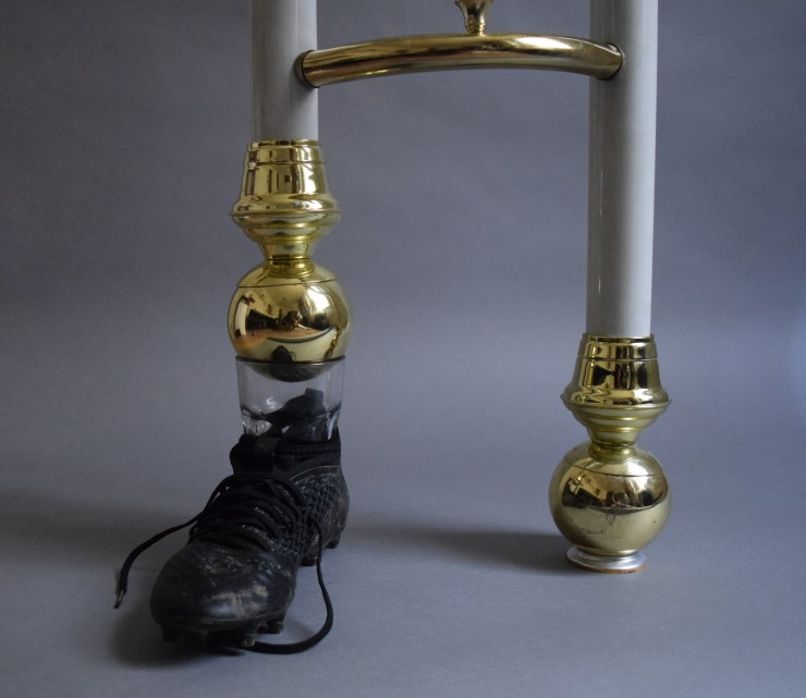 A stoneware self portrait bust and a glass filled with water on either ends of a wooden beam balanced on one pole of an inverted found bedframe. The end of the other pole is inserted in a glass placed inside a soccer boot.