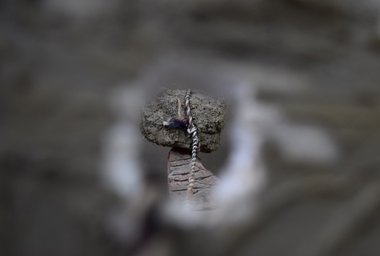 A lump of dried mud balanced on a brick on one side, a glass of water with a small chunk of clay balance on a small piece of wood on the other side and a piece of styrofoam with a hole and smeared with clay in between, separating the two. A rope passing t
