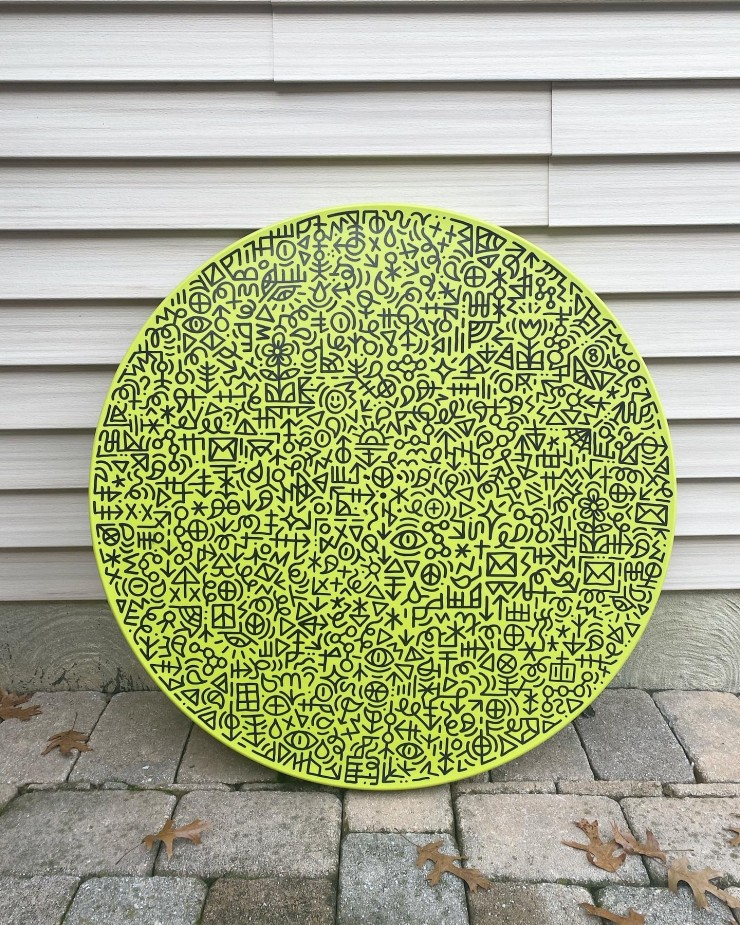 Upcycled green plastic circle with hand drawn black details