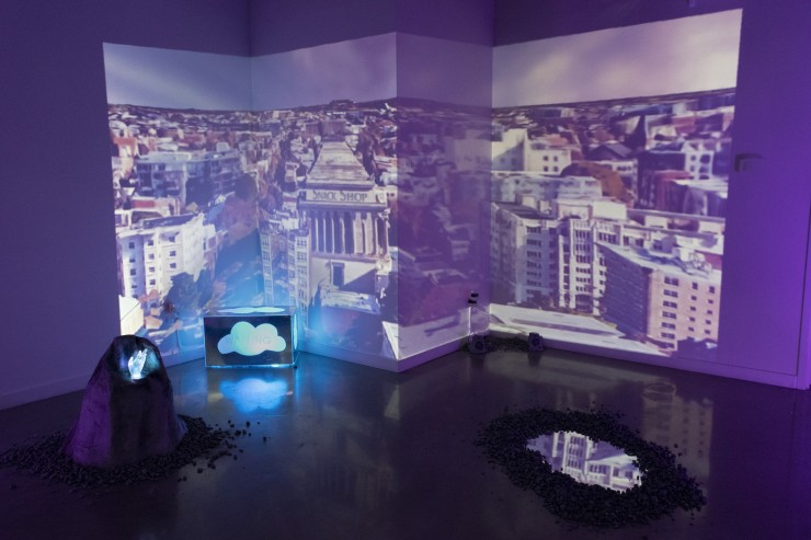 Photograph of installation depicting video projection-mapped around wall with light sculptures nearby.