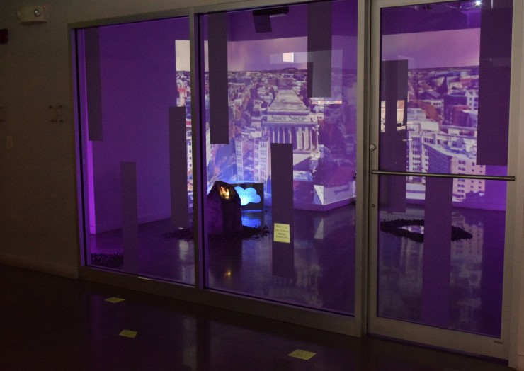 Photograph of video projection on glass consisting of multiple rectangles into which various objects are projected.