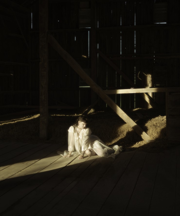 This is a portrait oriented digital photograph. The figure lays in a beam of warm sunlight, her hands touch the wooden floorboards and light is seen creeping in through the slats of the barn wall behind her.