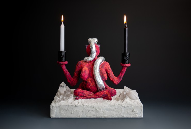 This piece is a figure seated on sand with large clear quartz emerging from the sand, the figure is a red Earth Goddess with amethyst eyes holding two candles one black one white, a silver snake representing the Moon Goddess with clear quartz eyes slither