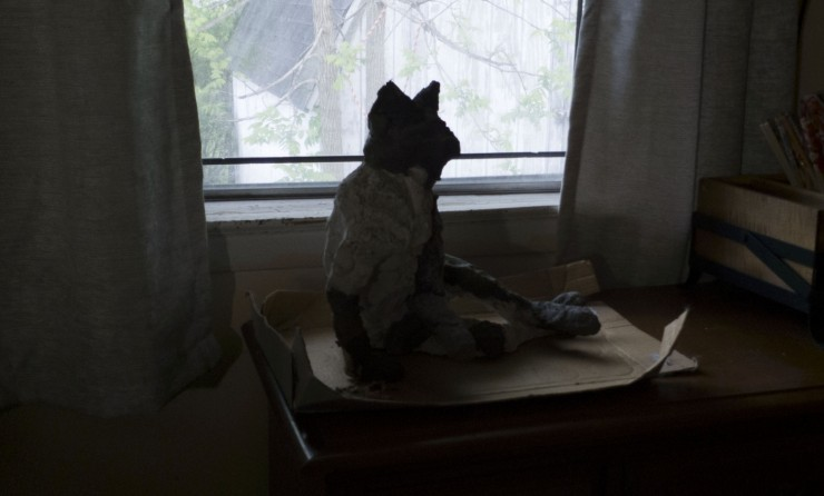 A multicolored sculpted cat sitting on a cardboard square in front of a window, backlit.
