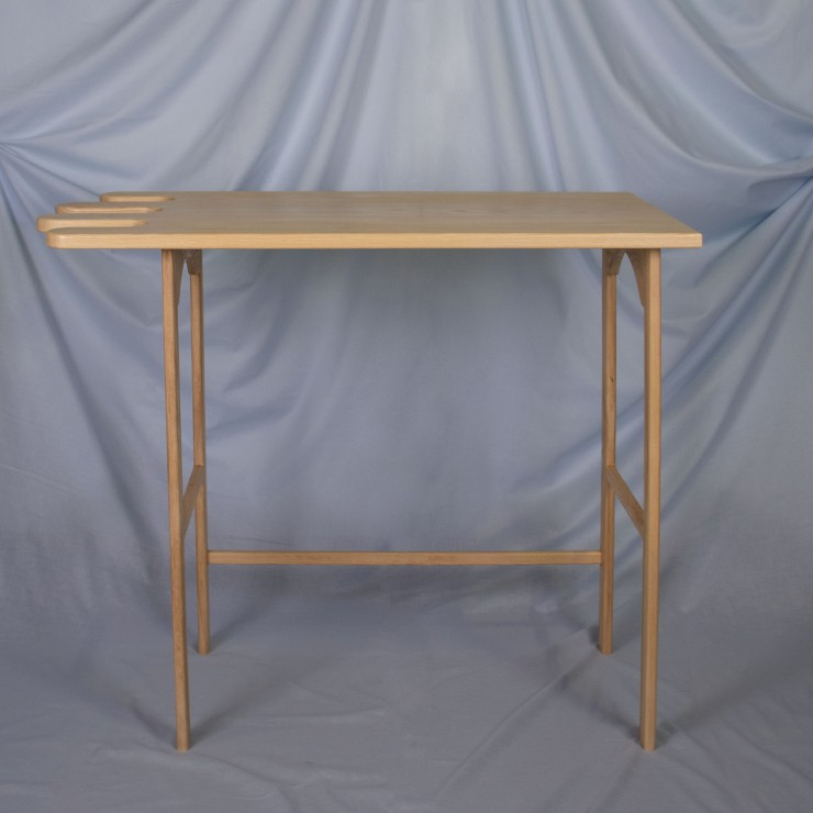 A light ash wood desk sits on a powder blue, fabric backdrop. The desk is oriented straight on to the viewer. The desk has four straight legs with a crossbar in the lower third of both sides and an arch at the top of each side. There is a supporting cross
