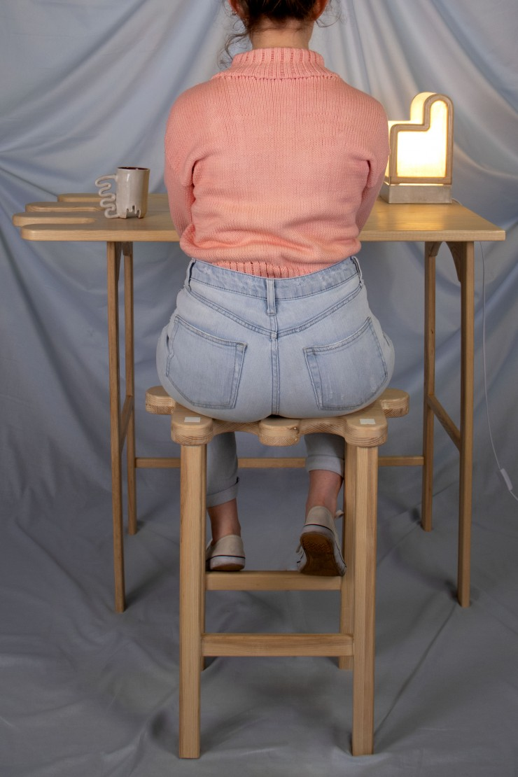 A light ash wood desk and stool ensemble sits on a powder blue, fabric backdrop. The model wearing the pink sweater is sitting on the stool, now facing the desk with their back to the viewer. The ceramic mug sits to their left on the desk and the illumina