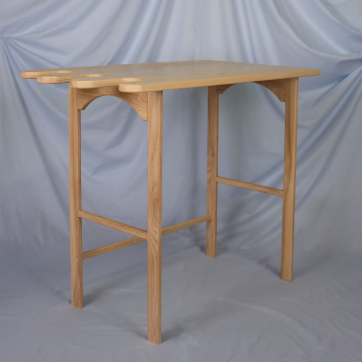 A light ash wood desk sits on a powder blue, fabric backdrop. The front left corner of the desk is angled towards the viewer. The desk has four straight legs with a crossbar in the lower third of both sides and an arch at the top of each side. There is a