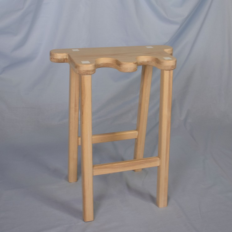 A light ash wood stool sits on a powder blue, fabric background. The stool is placed on an angle, with the left leg towards the viewer. There are four, square, angled legs and support bars spanning the lower third of the front and back legs. The seat of t