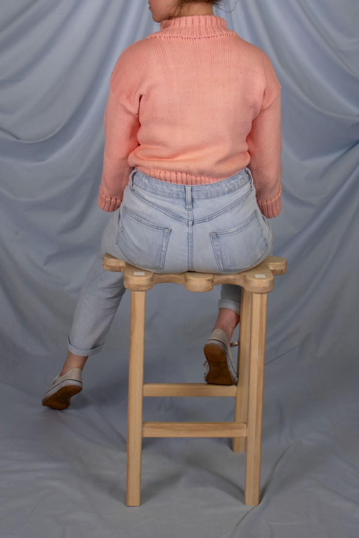 The light ash wood stool sits on a powder blue, fabric backdrop. The back of the stool with the three protruding fingers is facing the viewer. A model wearing a bright pink sweater and light jeans is sitting on the stool, facing away from the viewer. Thei