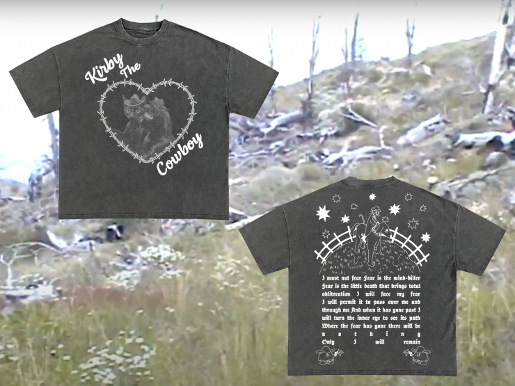 """A black t-shirt with a picture of a black cat wearing a cowboy hat staring deeply into his reflection. The cat is enclosed in a barbed wire heart. At the top and bottom of the heart is cursive text that reads """"Kirby the Cowboy"""". On the back of t"""