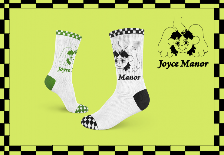 two socks on a bright slimy green background that say Joyce Manor with have a cherub head with wings underneath that text. There is a foot resting on the cherub's head but the cherub is smiling and happy. checkers line the top and toes of the socks. Ther