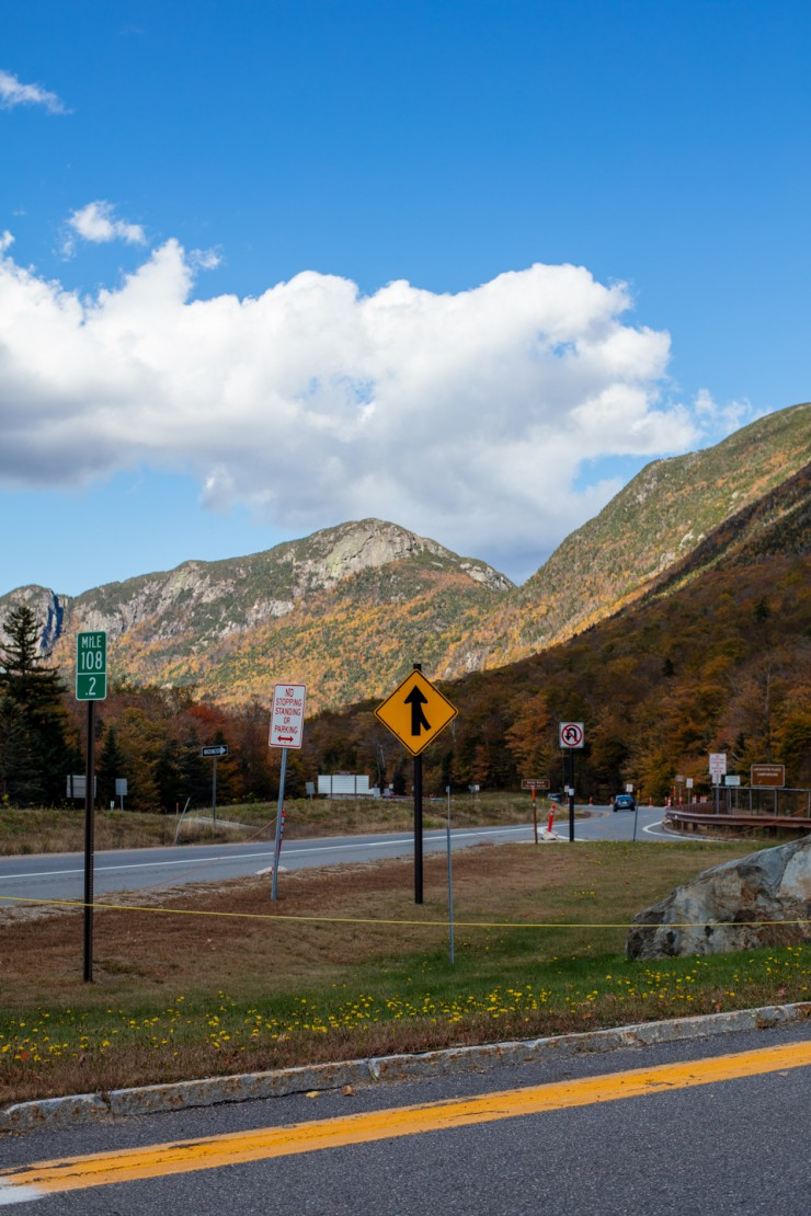 Risher_Wondrous (3 of 7)- This is a portrait oriented digital photograph made on a highway in the mountains during the day. The sky is blue with a large white cloud. In the background, the mountains are covered with colorful autumn trees. In the foregroun