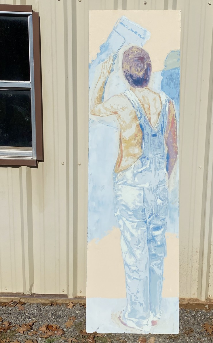Figure who is painting a wall with a roller is seen from behind, carved into joint compound, whilst on the back side, carved into the dry-wall is a message to viewers.