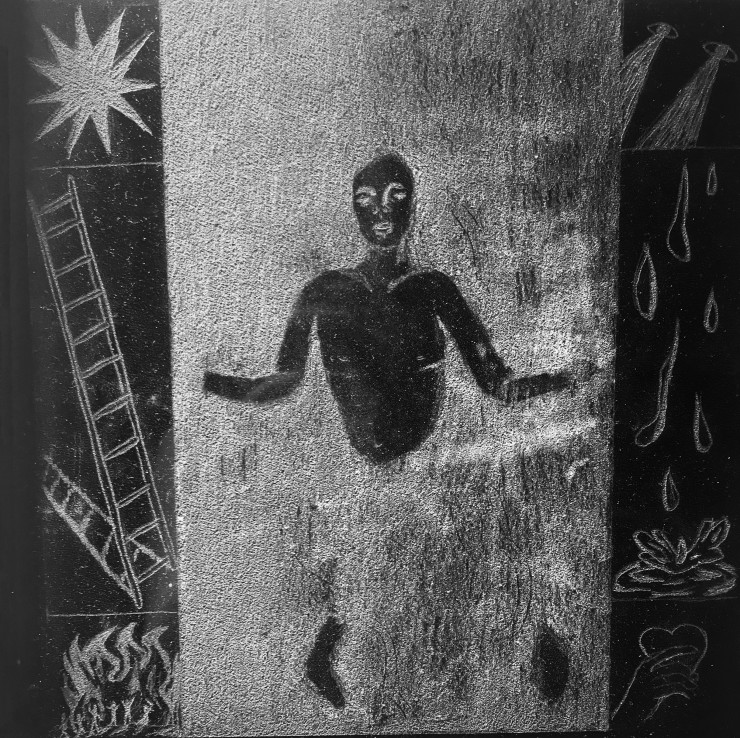 A piece of black opaque acrylic etched onto it is an image of  a figure submerged in a void flanked on either side by panels depicting: a star, a ladder, small figures engulfed in fire, a set of eyes, water droplets, and a hand holding a heart