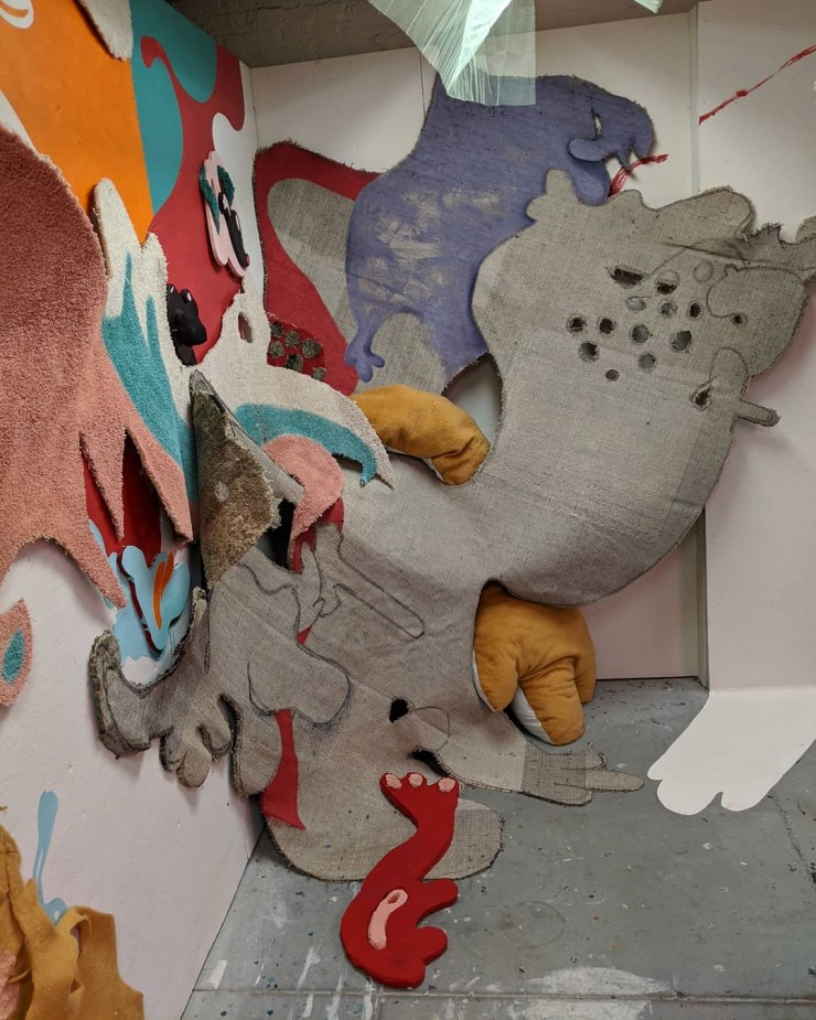 "A view of the installation facing a corner. The backside of a shaped carpet is draped over the corner, connecting from one wall to the other and touching the floor. On the left side, it lays on top the end of ""Studio Creature."" In the center is"