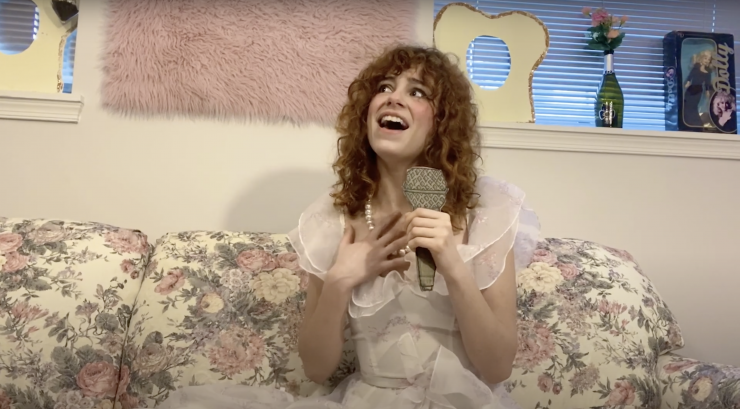 the artist in a pink dress, sitting on a couch and holding a cardboard microphone