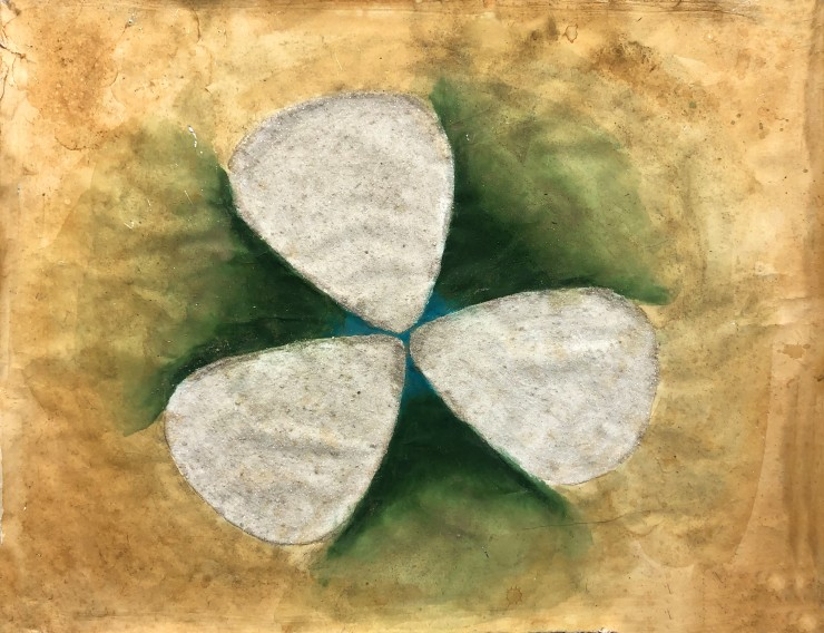 Three off-white guitar pick shapes made of glass bead gel and sparkly mica schist nearly touch at the tip of each pick, forming a flower shape. Green radiates from the center of the picks and fades into rust ink which extends to the edge of the paper.