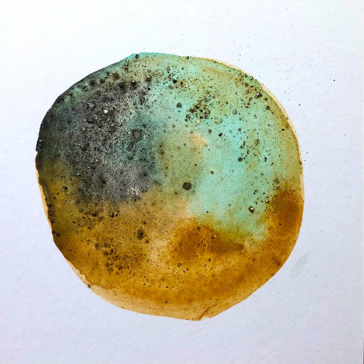 A circle with a watery blend of light blue, grey, and dark yellow with black sparkly rock sprinkled throughout.