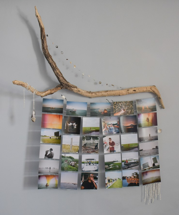 A collection of printed film photographs taken in my home town chained together and attached to a large piece of found driftwood, various things collected from the beach, and thrifted pearl and shell beads for 'decoration' all combined to form a curated i