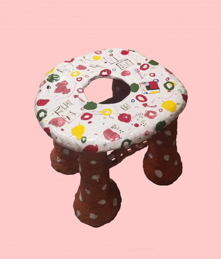 Image of a 'toilet'made of clay on light pink digitally imposed background. Four legged stool with a hole in the center. The legs are raw red clay with sparkly mica flake and white shiny glazed polka dots. The top is solid white glaze  with illustrations