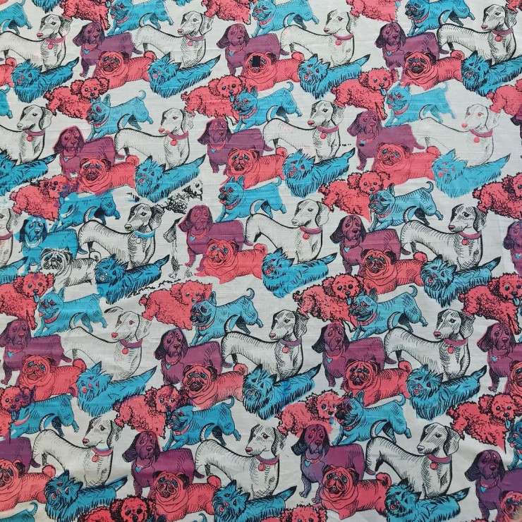 A repeating pattern of assorted dogs spread across a sheet of fabric. They're colored pink, blue, and purple.