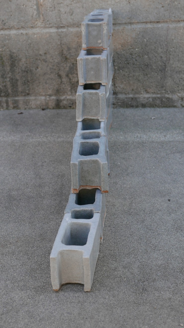 These ceramic cinder blocks were made to the scale of the maker's hand. In total there are twenty two of them. Each one of them is unique despite having been made the same way and covered in the same glaze. They have been stacked as if they were actually