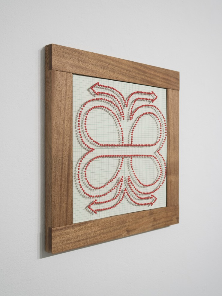 """A close-up of the two framed works. One contains many red map pins stuck into green graph paper to form the outline of a highway clover. The other contains an image of a blue car that is dented and a fabric tag that says """"made with love""""."""
