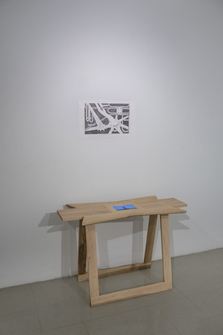 """A wooden table with a small screen in the center of the tabletop. The tabletop is in a shape that is similar to a """"burst"""" and an intersection of four roads. The screen is showing the tabletop standing vertically at the top of a grassy hill. Above the tabl"""