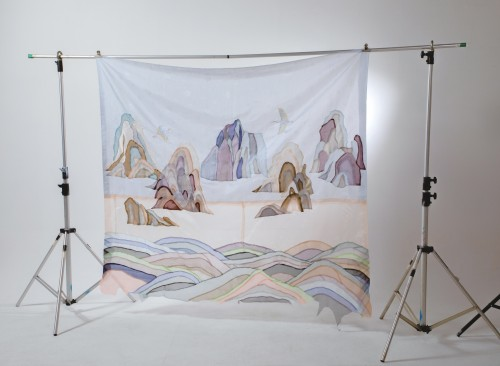 Hanging fabric that has waves on the bottom and five mountain peaks on the middle range with two flying cranes.