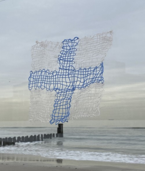A small lace-like weaving of a blue cross and white background seems to float above the shoreline of urban beach in winter. A woman wearing a gray coat stands on a jetty in the distance appears to be gazing at a lacey weaving of two white hills on a blue