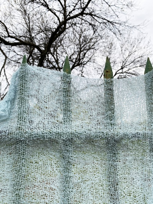 An airy blue weaving hangs over a cemetery fence with pointed bars the weaving is pressed tightly against the fence creating a mysterious shadow of the iron bars. It is overcast and the trees above the fence are are bare.