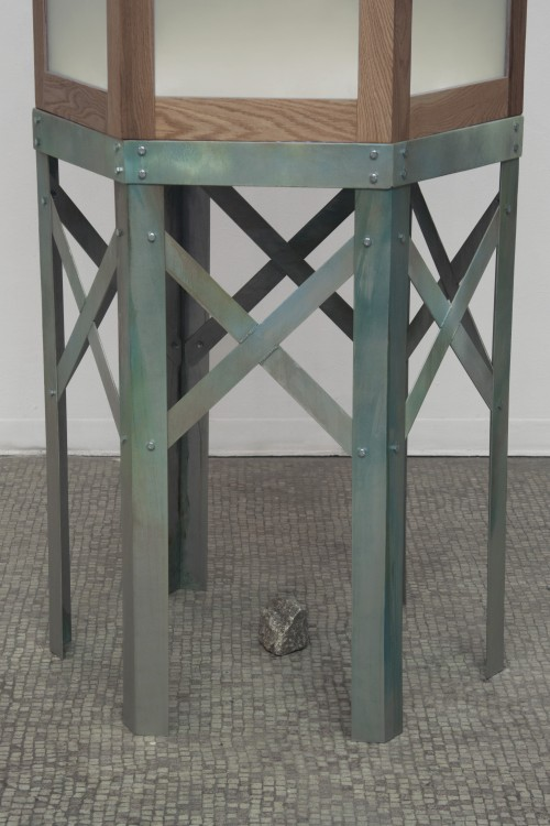 This work is a sculpture of a large, hexagonal tower. The bottom half of the tower has long, aluminum legs with crossing supports. Green-blue patina drips down the legs of the sculpture. On top of the tower, warm light glows from large windows framed by o