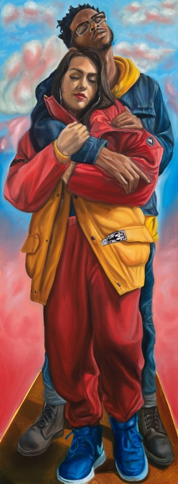 A couple embraces one another while standing. The female in the front has long dark brown hair that covers most of her silver hoop earrings. She wears an oversized red and yellow jacket  with a small lobster and heart on it and oversized red pants. The sa
