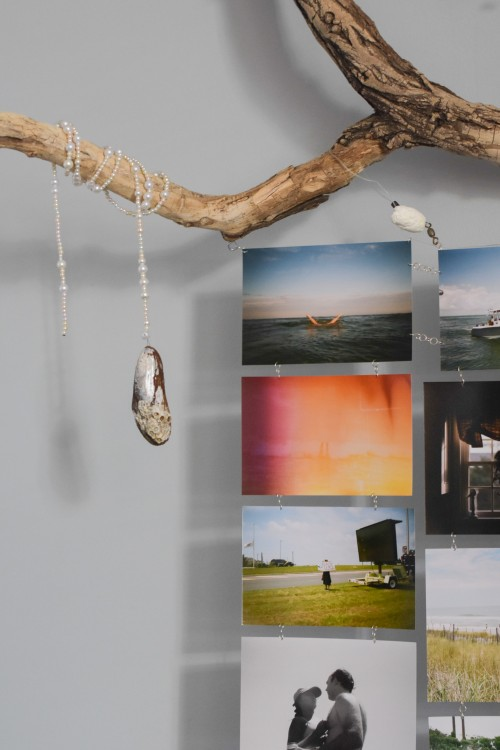 Detail shot of chained photos attached to found driftwood with pearl string and found shell.