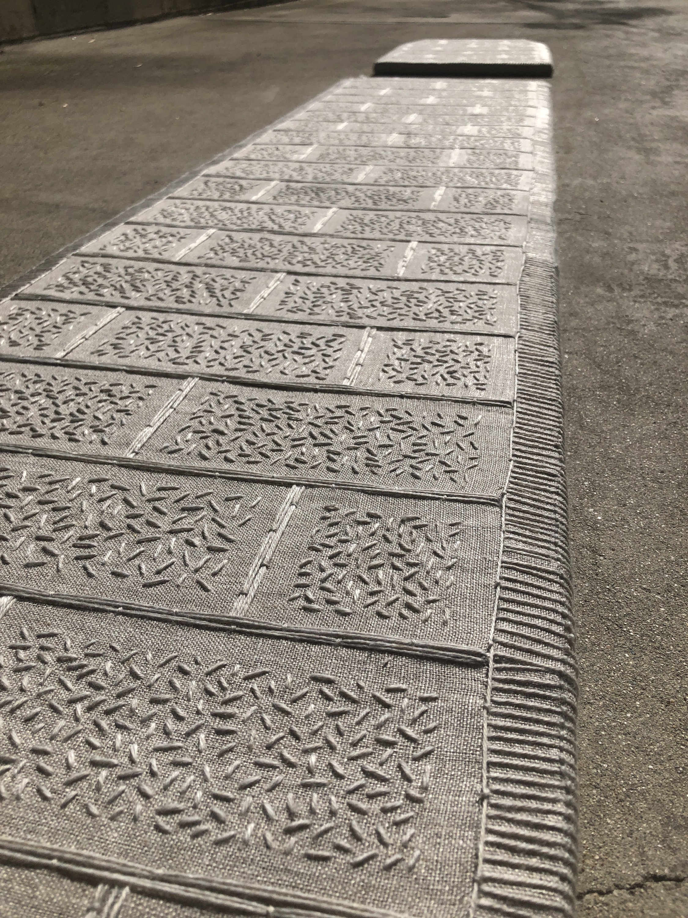 Traffic Island is a reconstruction of an intersection island. The piece is made of two main slabs of embroidered rectangular piecework wrapped around a solid backing. The pieces together resemble the object they were modeled from but differ in function an