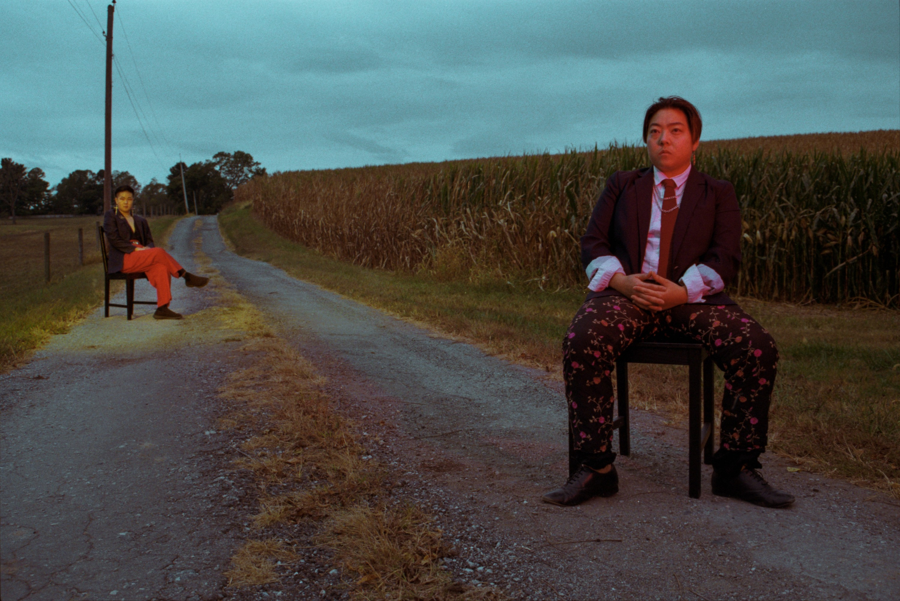 Two people sitting on chairs on a road